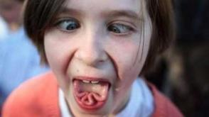 girl contorting her tongue and crossing her eyes