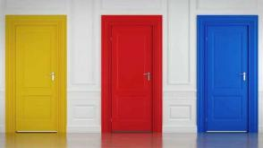 Photo of three closed doors, painted yellow, red and blue, set in a white wall.