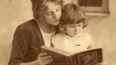 Vintage photo of a mother reading a book with her daughter.
