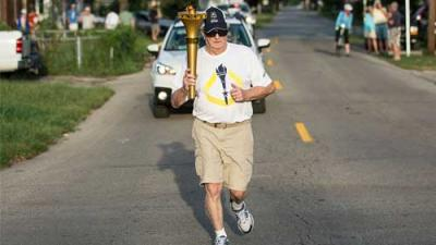 Photo of an elderly man running with a torch followed by cars.