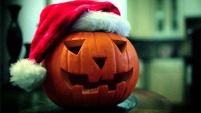 Photo of a carved jack-o-lantern wearing a santa hat.