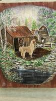 Close up photo of a painting of a llama in front of a barn