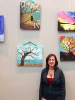 Sheila Maxwell posing in front of her canvases.