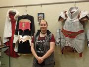 Photo of artist Autumn Fagenbaum in front of her costumes.
