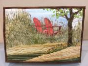Small display quilt of red chairs by Lake Michigan.