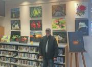 Photo of the artist in front of several paintings