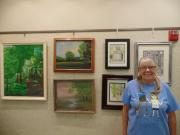 Photo of the artist with her paintings.