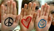 Photo of girls with marker drawings on their hands: peace, a heart, smiley face
