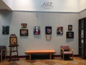 Photo of several paintings arranged on the art wall at the Rensselaer Library