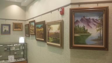 Photo of several paintings along wall. Foremost is a lake with mountains.