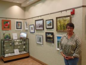 Photo of the artist with photographs along the wall in the background
