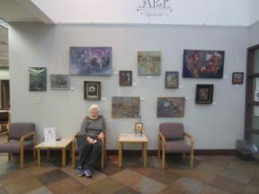 Photo of the artist with several paintings on the art wall.