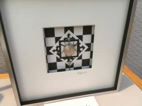 Photo of six inch silver frame with an arranged silver piece within.