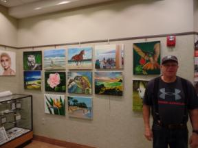 Photo of the artist and several paintings on a gallery wall.