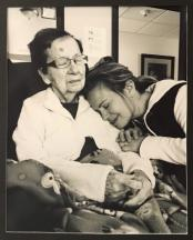 Photo of a young woman holding her seated grandmother.