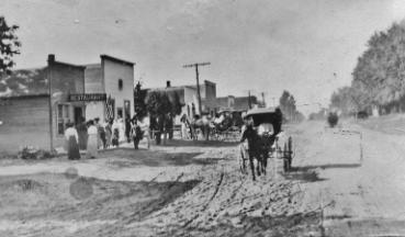 Photograph of a horse buggy on a dirt road and women in front of a restaurant.