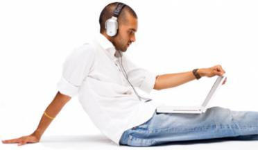 Man listening to audio while working on a computer