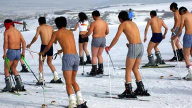 Photo of skiers on slope, all wearing shorts with no shirts or belly shirts.
