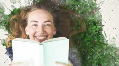 Photo of smiling girl reading book on grass