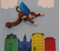 Curious George flying over a city